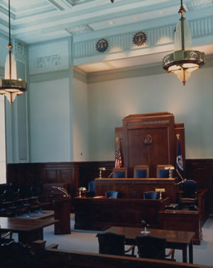 I created several values of a warm grey to enhance the inlaid wood. To ensure the space was lit bright enough at night, metal halide fixtures were mounted on the side walls and to give the judge drama, up lights were mounted behind his podium.